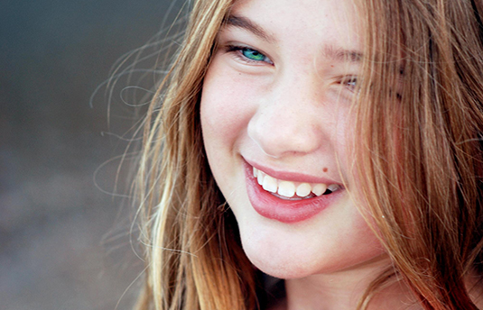 young girl smiling showing teeth