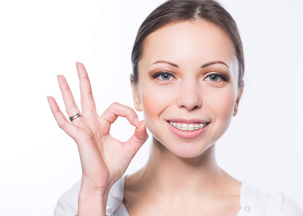 Smiling woman with braces giving the okay hand signal