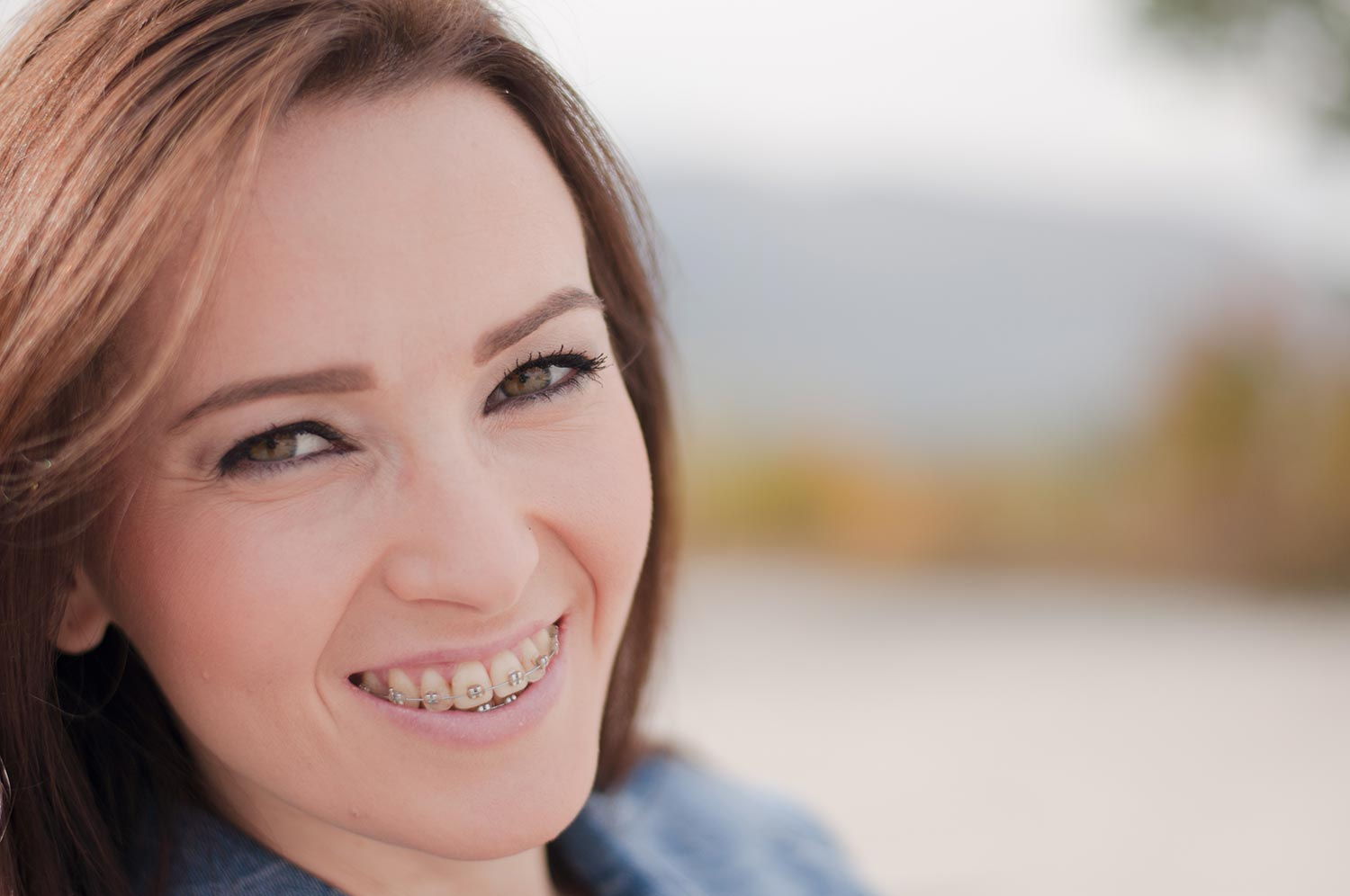Young woman smiling with metal braces on her teeth