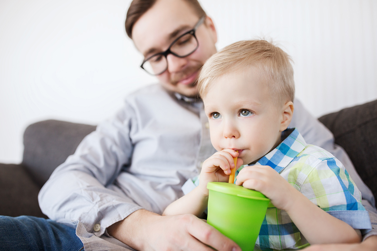 Father with son drinking through a straw from a plastic cup.