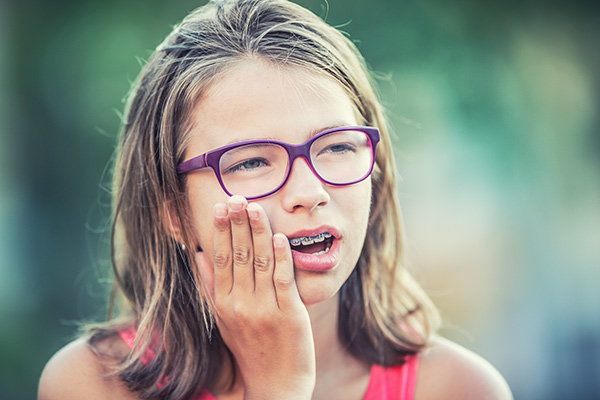 Girl with braces and painful expression holding her cheek from tooth pain.