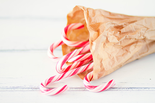 Peppermint candy canes in a bag resting on a table.