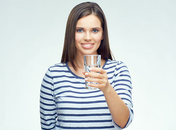 Young woman drinking water for dry mouth with braces.