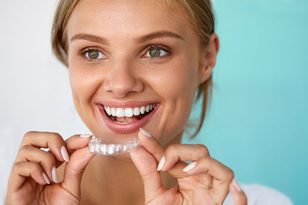 A smiling woman placing an Invisalign aligner in her mouth.