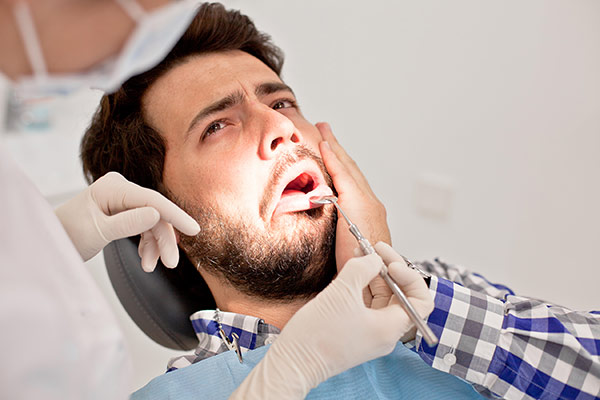 A man with jaw pain at the orthodontist