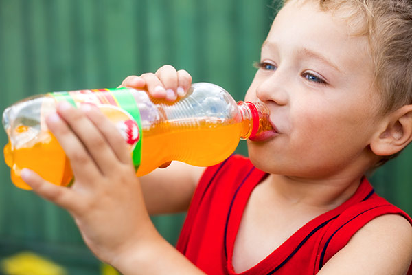 A child with bad dental habits drinking a sugary soda.