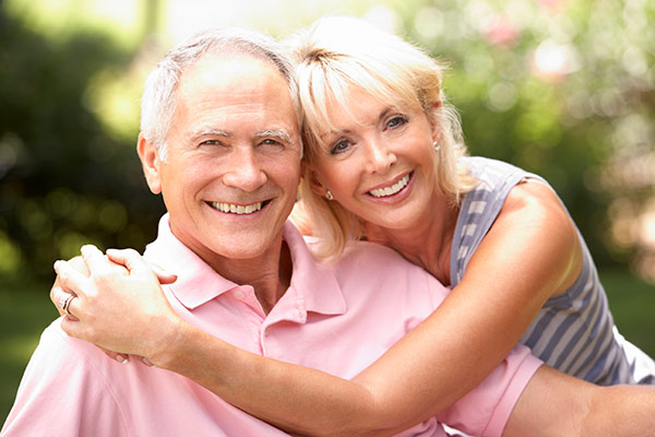 A senior couple using Invisalign for seniors to improve the alignment of their teeth