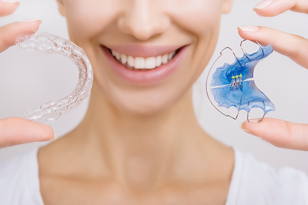Woman holding two types of retainers for use after braces