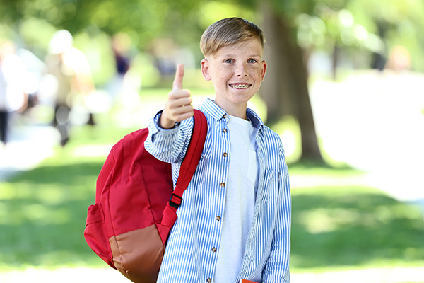 A child wearing braces and a red backpack giving a thumbs up.