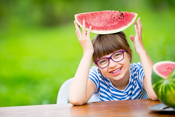 Girl holding a watermelon after getting summer braces.