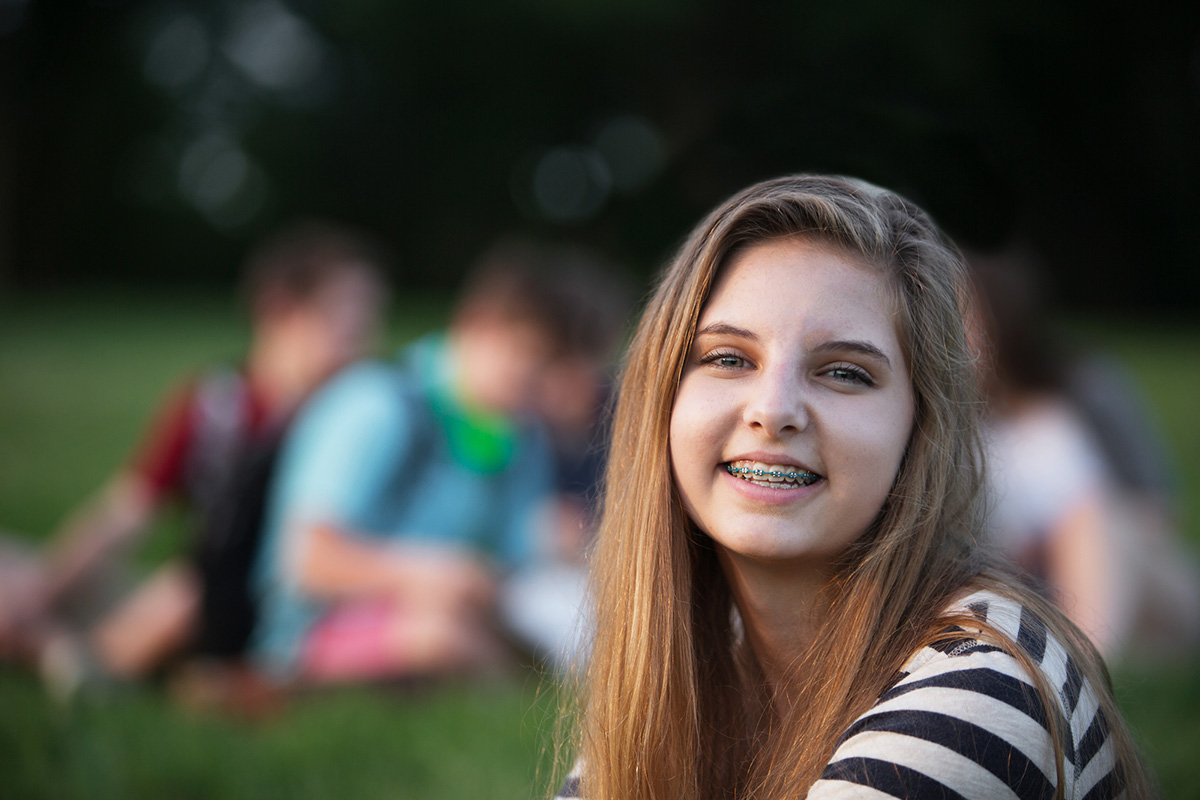 Teen girl smiling with braces in front of friends sitting on the grass.