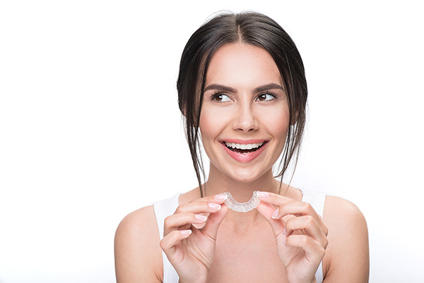Smiling woman with an Invisalign clear aligner.